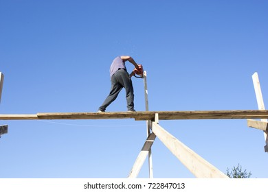 Man works at height. Dangerous work at altitude. A man works without protection. Violation of safety precautions. Dangerous work of the chainsaw at altitude.
