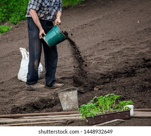 A man works with the land in the garden .