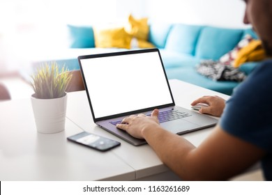Man works on a blank screen laptop in a home interior - mockup, template