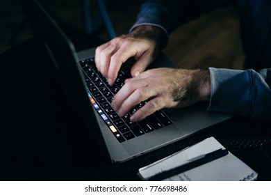 a man works on a laptop in the dark, does something illegal, hacks