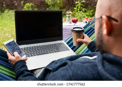 Man works on laptop in the garden sitting on hammock and using phone and drink coffee. Empty screen of laptop and mobile with mock up. Home office with relax and nature. Freelancer outdoors. Close up.