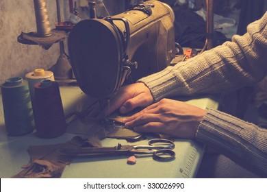 Man works on sewing machine.