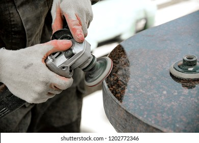 A man works polishing a marble stone with an angle grinder. iznotovlenie monuments of natural stone
