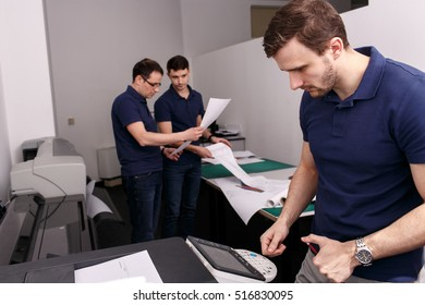 Man works with a printer while his colleagues discuss something on the background