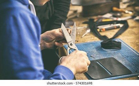 A man works with scissors and cuts something