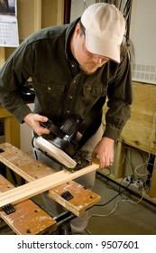 Man in workshop with skillsaw cutting a piece of wood