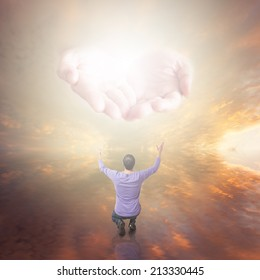 Man worshiping. The Hands of God with light coming from the sunset sky