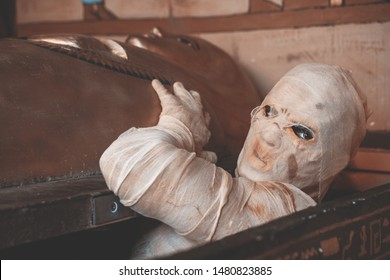 man wrapped up with bandages as a mummy halloween costume, crawls out of the sarcophagus