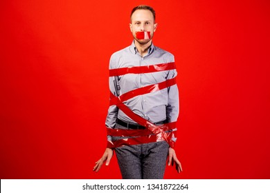man is wrapped in red tape. kidnapping or fear concept.