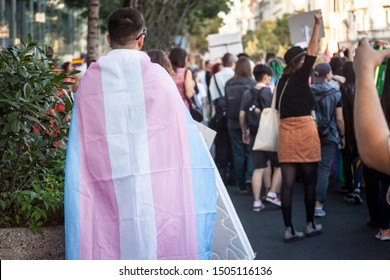 Man wrapped in a transsexual flag seen from behind during a gay pride. This flag is one of the symbols of LGBTQ and transgender people and community