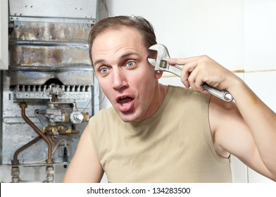 The man with a wrench thinks of repair of a gas water heater