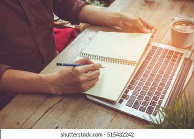 Man write on notebook with laptop vintage tone.