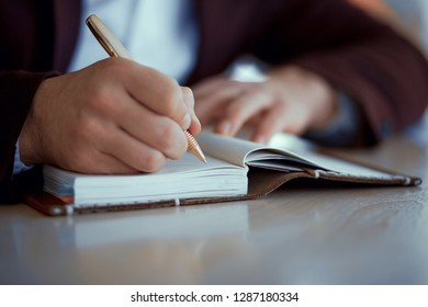 A man writes a gold pen in a leather notepad at a wooden table. Front view close-up