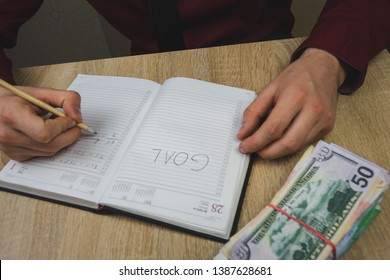 man writes his goals in his notebook, on the table is a bundle of cash.