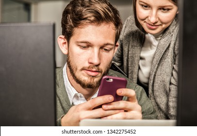 man writes message on his smartphone colleague looks at him. they sit between monitors in office environment. focus on the man's face