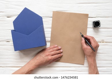 Man is writing by a quill pen on blank letter page near a post box on a white wooden table background.