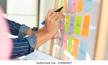 man schreibt mit der rechten Hand auf Notizbücher, die an weißem Brett haften. trägt ein blaues Hemd mit Strip. Hände und Notizbücher.