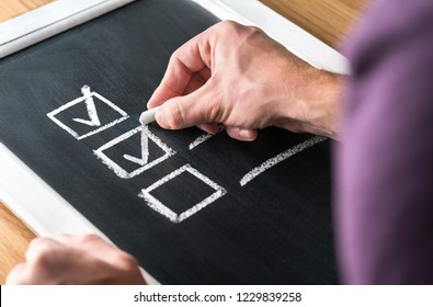 Man writing checkmark to checklist on blackboard. Document of finished work and completed tasks on chalkboard. Check list for planning and keeping score. Project management and leadership. Tick mark.