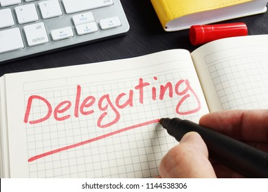 Man is writing delegating in the notepad. Delegate concept.