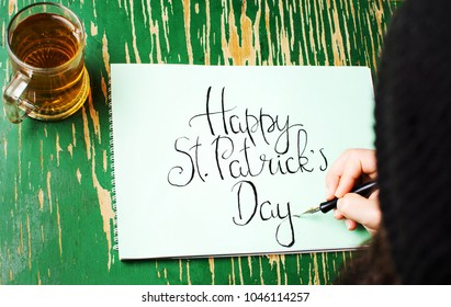 Man writing a Happy St Patrick day calligraphy card