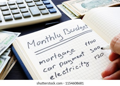 Man is writing Monthly Budget Plan. Home finances.