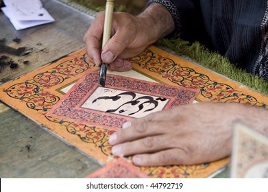 a man writing a name with traditional arab characters in a beautiful card