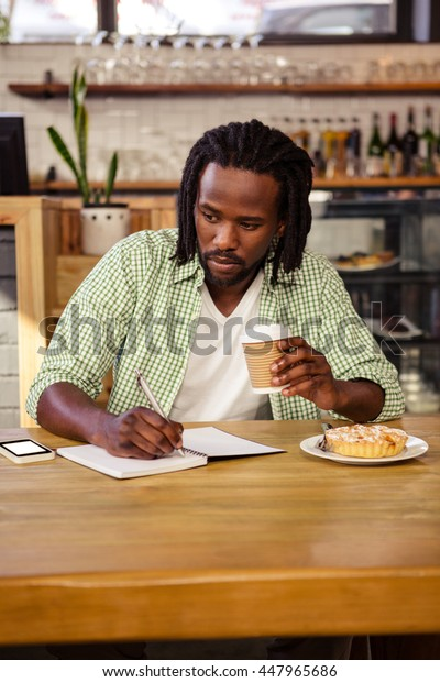 Man writing in a notebook in a cafe