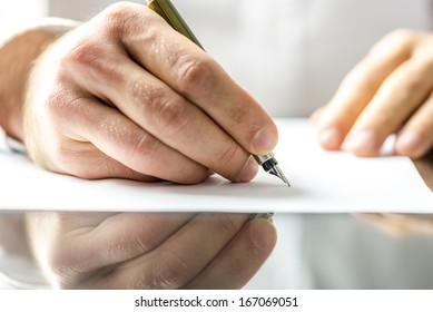 Man writing on a blank paper with ink pen.