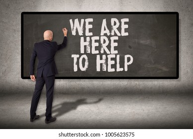 Man writing on chalkboard on concrete wall We Are Here to Help