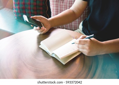 Man writing on  notebook and hold smartphone on wood table with coffee cup,  in morning time