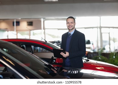 Man writing on a notepad beside a car in a garage