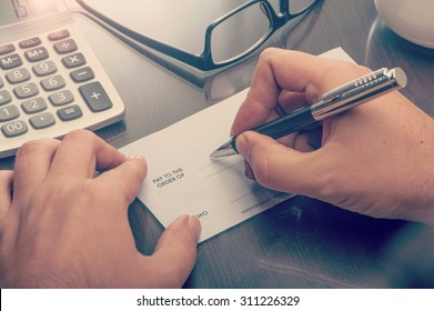 Man writing a payment check at the table with calculator and glasses