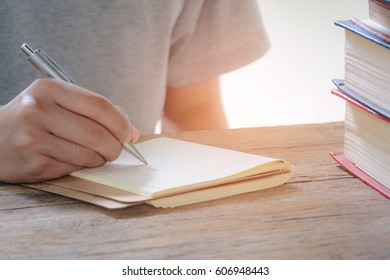 Man writing pen in book on old wood table at home