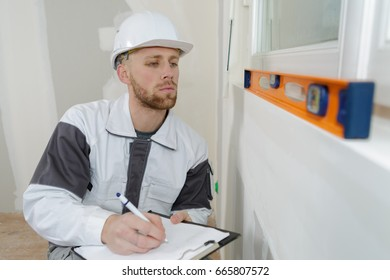 man writing the result from the spirit level