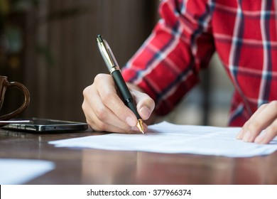 A man is writing/signing on a paper. Focused on a hand with pen.