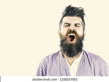 Man with yawning sleepy face on white background. Hipster with beard and mustache with messy hair wears bathrobe, close up. Morning yawning concept. Guy awake with mouth opened in yawn, copy space.