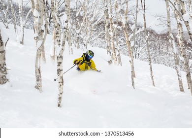 Man in yellow with backpack skiing steep hillside with many trees and soft powdery snow. The backcountry skier is on Niseko Mountain in Hokkaido, Japan.