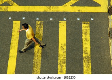 Man in yellow crossing intersection with yellow stripes