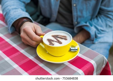 Man with a yellow cup of coffee, morning by the river on the pier with hot drink