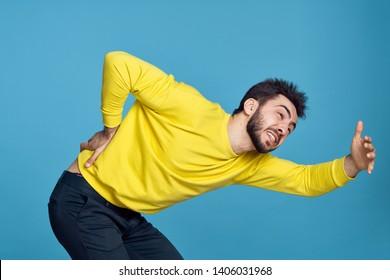 a man in yellow has a backache