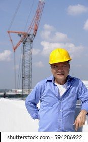 A man with a yellow helmet smiles at the camera as he works