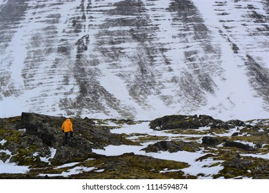 A man with a yellow jacket climbing rocks next to a steep drop off