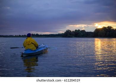 A man in a yellow  jacket on kayak enjoying the sunset