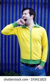 man in yellow jacket is yawning