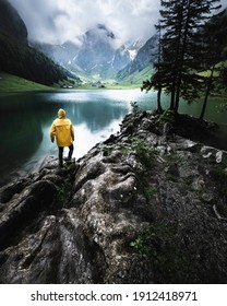 Man with a Yellow raincoat Hiking in the swissalps and enjoying the moment.