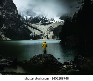 A man in a yellow raincoat on a rock looking over a lake towards big snow covered mountains seeming very little in a big world in a moody edit during a rainy misty and foggy day at lago di braies