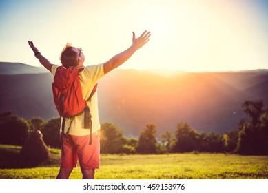 Man in yellow shirt, sunglasses and red backpack holding arms outstretched on mountain meadow in sunset