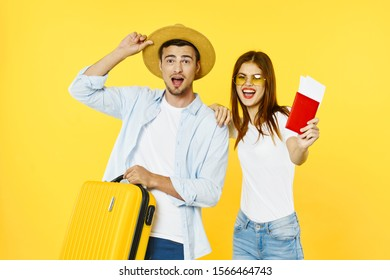 A man with a yellow suitcase straightens his hat on his head and a woman holds passport tickets on an airplane