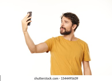 A man in a yellow T-shirt is looking at a mobile phone in his hand
