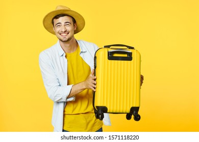 A man in a yellow T-shirt and shirt with a suitcase in his hands and a hat on his head